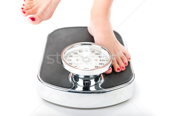 Stock photo: Young woman standing on a scale