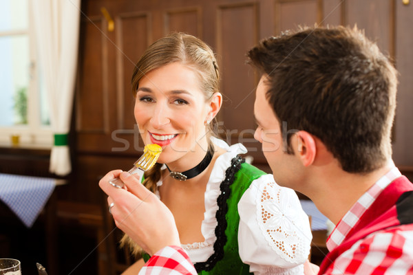 Young couple in traditional Bavarian Tracht eating in restaurant or pub Stock photo © Kzenon