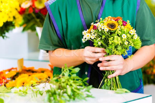 Female florist in flower shop Stock photo © Kzenon