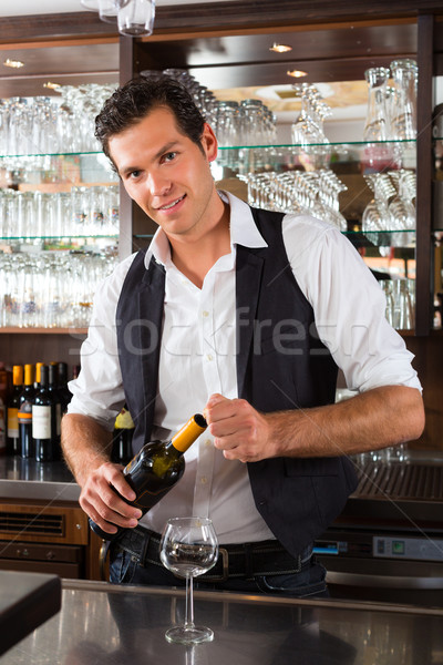 Barman standing behind bar with wine Stock photo © Kzenon