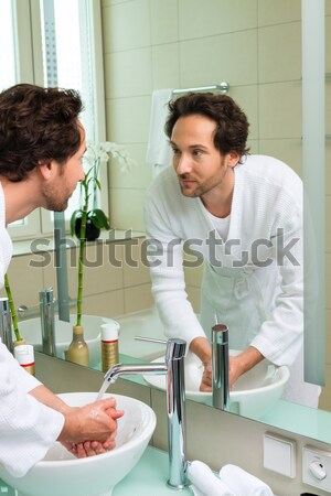 Young man in bathrobe in hotel bathroom Stock photo © Kzenon