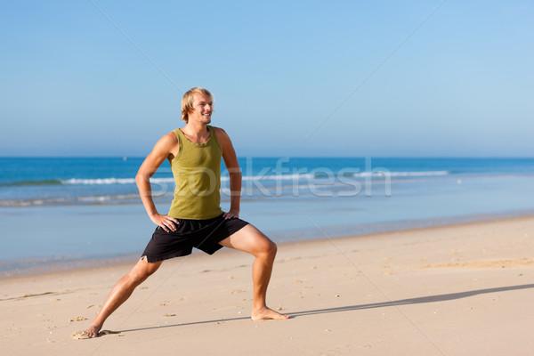 Hombre gimnasia playa jóvenes cielo mar Foto stock © Kzenon