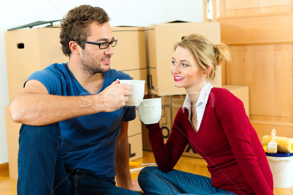 Young couple having break while moving in Stock photo © Kzenon