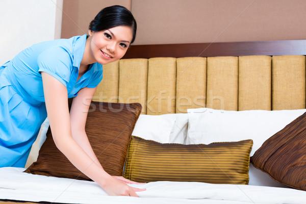 Chambermaid making bed in Asian hotel room Stock photo © Kzenon