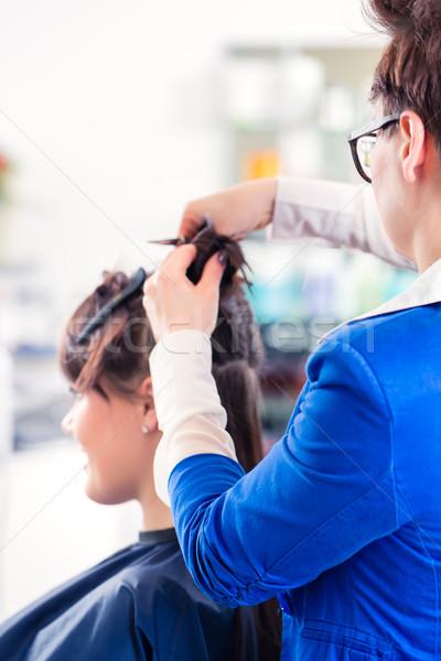 Hairdresser styling woman hair in shop Stock photo © Kzenon
