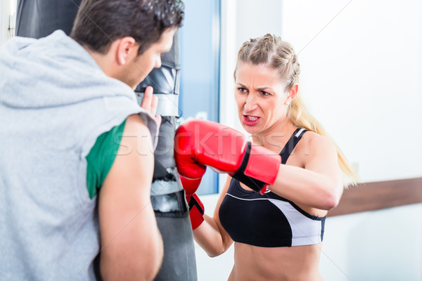 Young woman with trainer in boxing sparring Stock photo © Kzenon