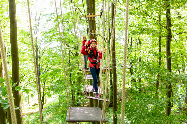 Teenager girl climbing in high rope course or parl Stock photo © Kzenon