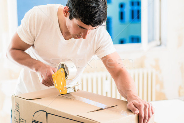 Man or handyman taping packing case Stock photo © Kzenon