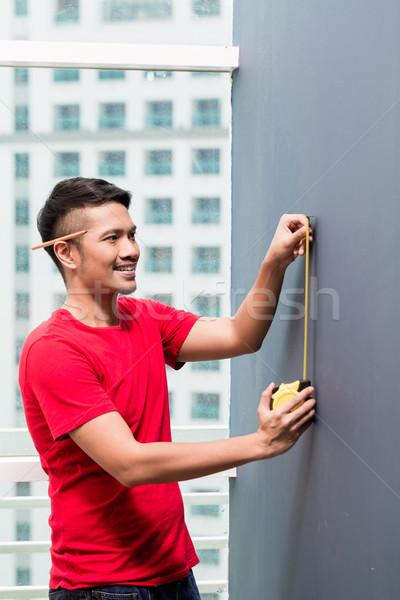 Jeunes indonésien homme mètre à ruban gratte-ciel bâtiment Photo stock © Kzenon