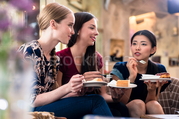 Stock photo: Three young women eating cake indoors