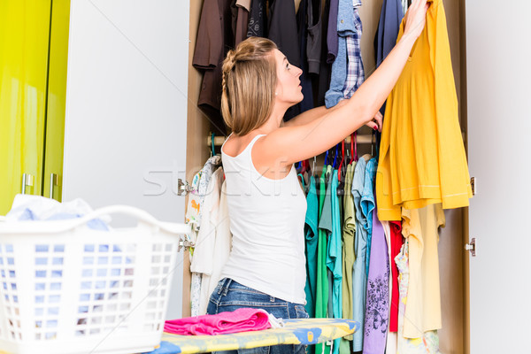 Woman putting shirt after laundry back into wardrobe Stock photo © Kzenon