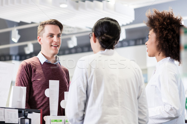 Happy customer talking with two helpful pharmacists in a contemp Stock photo © Kzenon