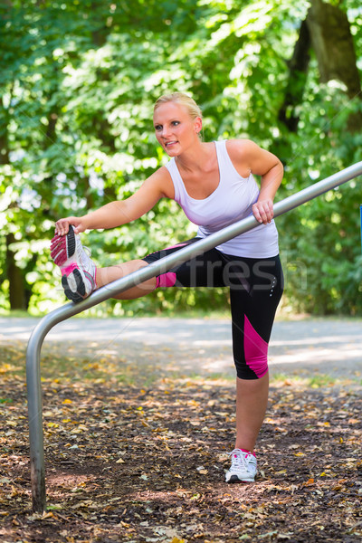 Young woman stretching before sport on fitness trail Stock photo © Kzenon