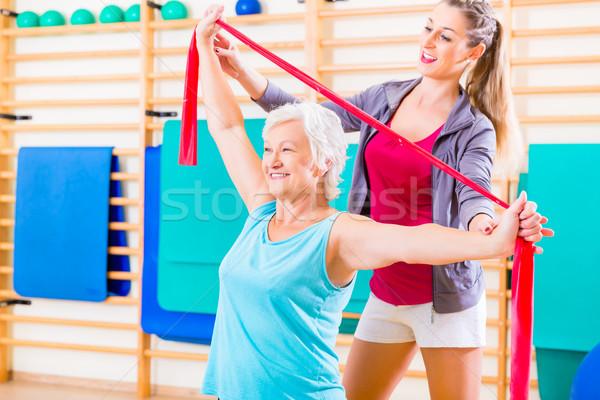 Idős nő zenekar fitnessz tornaterem személyi edző Stock fotó © Kzenon