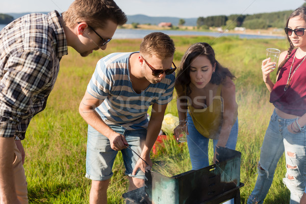 Group of friends having BBQ at lake in summer Stock photo © Kzenon