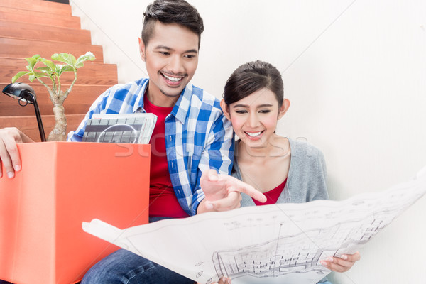 Asian couple with ground plot planning arrangement of new apartment Stock photo © Kzenon