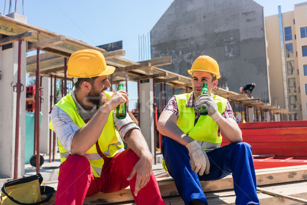 Two young workers drinking a cold beer during break at work Stock photo © Kzenon