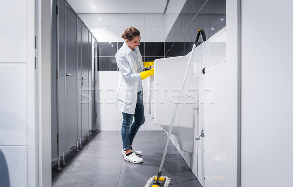 Janitor woman cleaning urinals in public toilet  Stock photo © Kzenon