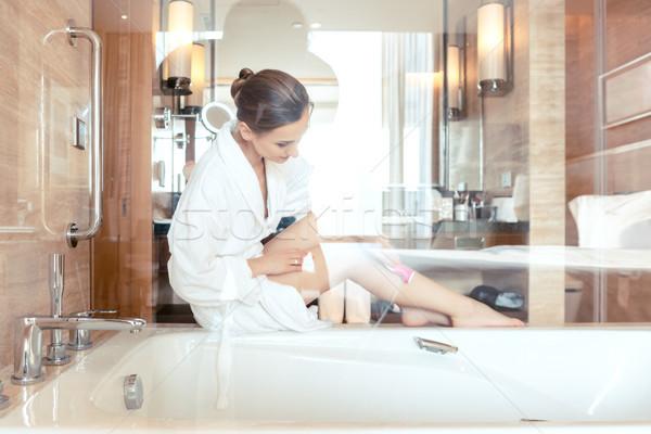 Woman removing hair by shaving her legs in bathroom of hotel Stock photo © Kzenon