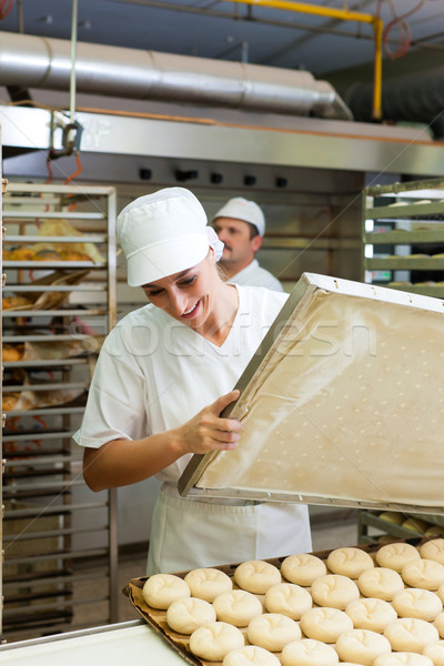 Female baker baking bread rolls Stock photo © Kzenon