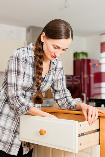 Young woman is assembling a cupboard Stock photo © Kzenon