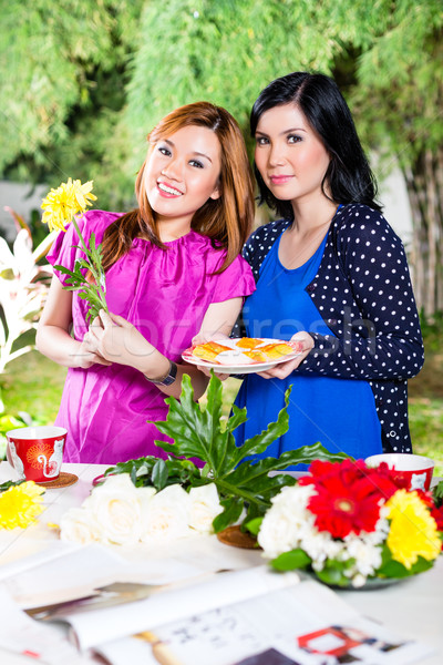 Two Asian girlfriends with flowrers Stock photo © Kzenon