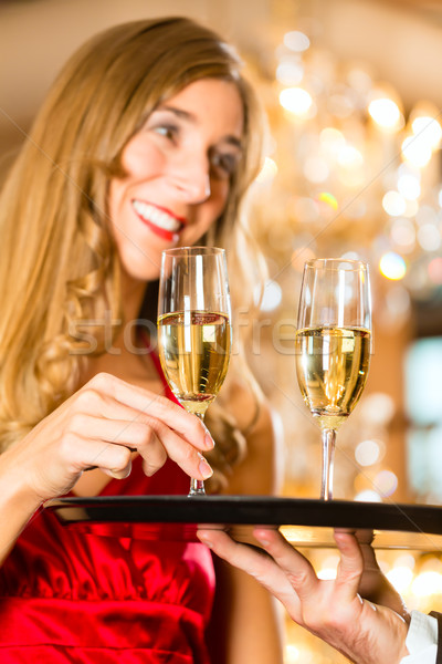 Waiter serves champagne glasses on tray in restaurant Stock photo © Kzenon