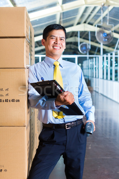 Young Indonesian worker in warehouse with Scanner Stock photo © Kzenon