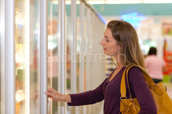 Donna supermercato congelatore sezione piedi guardando Foto d'archivio © Kzenon