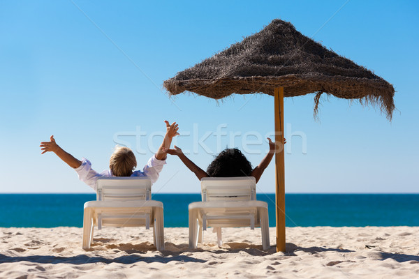 Couple on beach vacation with sunshade Stock photo © Kzenon
