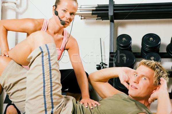 Edző fiatalember gyakorol tornaterem felügyelet személyi edző Stock fotó © Kzenon