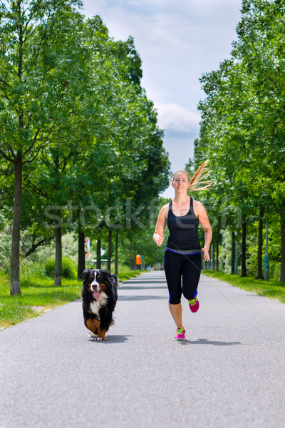 Sports outdoor - young woman running with dog in park Stock photo © Kzenon