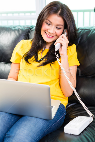 Asian woman using laptop and phone on couch Stock photo © Kzenon