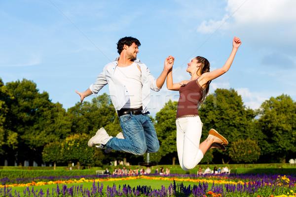 Tourist couple in city park jumping in sun Stock photo © Kzenon