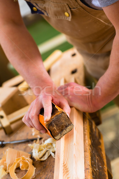 Carpenter with sanding block in carpentry Stock photo © Kzenon