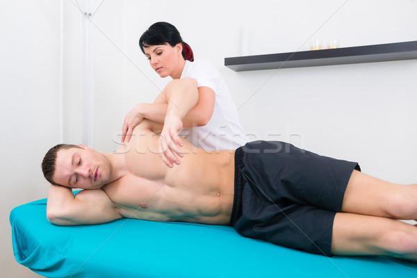 Physiotherapist or sport doctor patient in practice  Stock photo © Kzenon