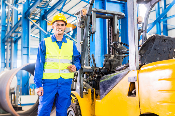 Forklift driver standing in manufacturing plant Stock photo © Kzenon