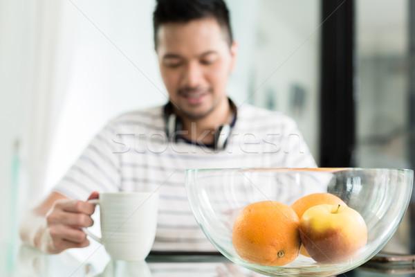 Indonesio hombre potable café desayuno escuchar música Foto stock © Kzenon