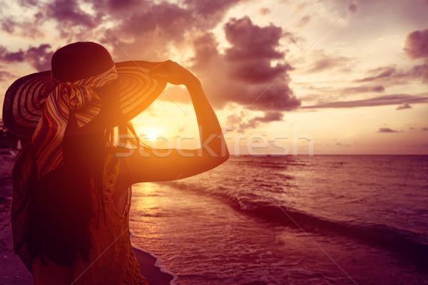 Tourist woman watching sunset at tropical ocean beach Stock photo © Kzenon