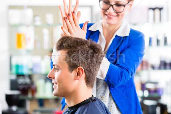 Hairdresser cutting man hair in barbershop Stock photo © Kzenon