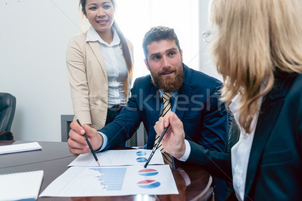 Business analyst smiling while interpreting financial reports sh Stock photo © Kzenon