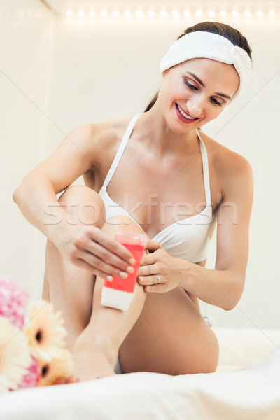 Fit woman waxing her legs with a portable roll-on depilatory wax Stock photo © Kzenon