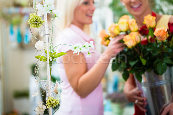 Two women looking at bouquet of roses in flower shop Stock photo © Kzenon