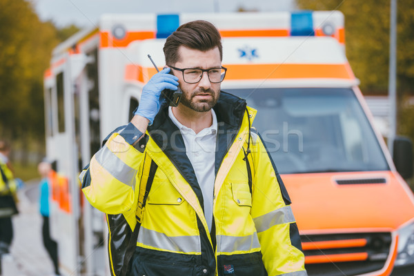 Medic talking to headquarter via radio in front of ambulance Stock photo © Kzenon
