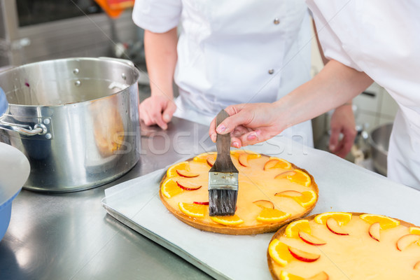 Fruit cakes being made by two pastry bakers Stock photo © Kzenon
