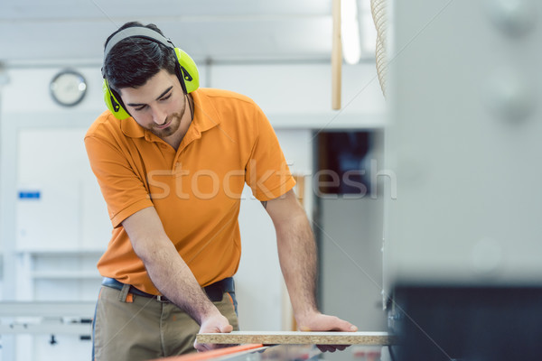 Carpenter working in furniture factory on machine Stock photo © Kzenon