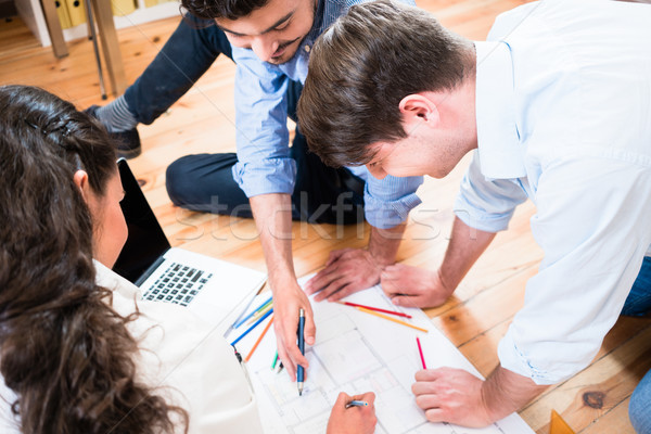 Architects bent over construction plans Stock photo © Kzenon