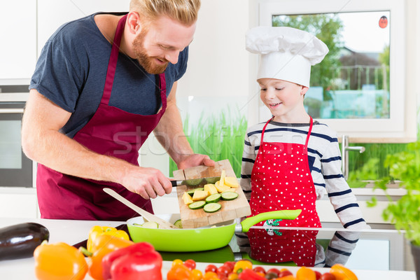 Father and son preparing food together in kitchen Stock photo © Kzenon