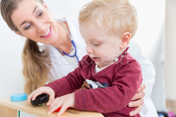 Cute active baby boy playing with toys during physical examination Stock photo © Kzenon