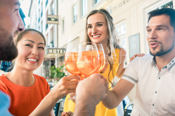 Four friends celebrating together with a refreshing summer drink Stock photo © Kzenon